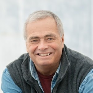 Image of smiling white man with short grey hair wearing denim shirt and black fleece vest